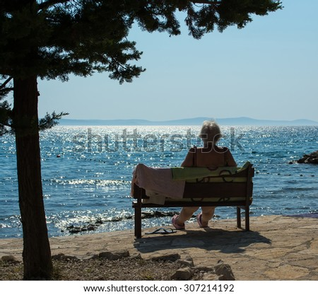 Old woman sitting on a bench on the beach. Enjoying summer time  - stock photo