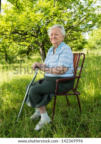 Old woman sitting on a chair on nature background