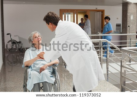 Old woman sitting on a wheelchair in a hospital while talking with the doctor - stock photo