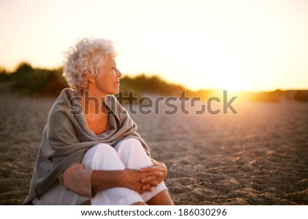 Old woman sitting on the beach looking away at copyspace. Senior female sitting outdoors - stock photo