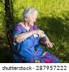Old woman spraying insect repellent on skin outdoor  - stock photo