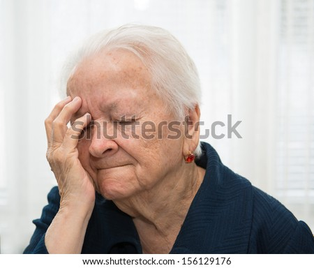 Old woman suffering from headache - stock photo