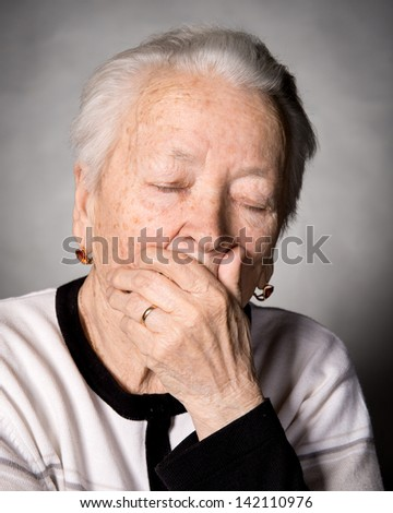 Old woman suffering from headache or toothache on a gray background