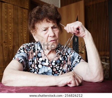 Old woman. Thinking elderly female at home - stock photo