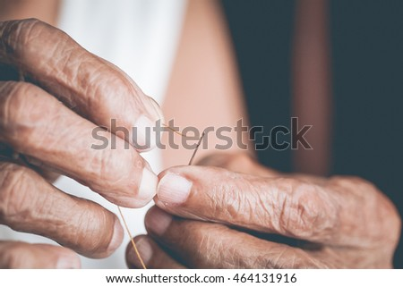 Old woman trying to thread a needle