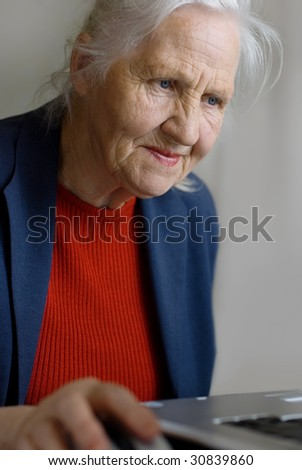 Old woman typing on laptop - stock photo