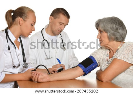 Old woman visitting  doctor and measure the pressure  on white background - stock photo