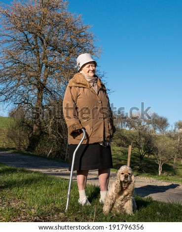Old woman walking in spring park - stock photo