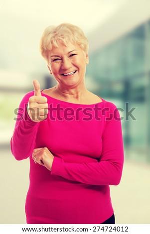 Old woman wearing pink shirt, showing OK - stock photo
