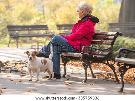 Old woman with a dog in autumn park - stock photo