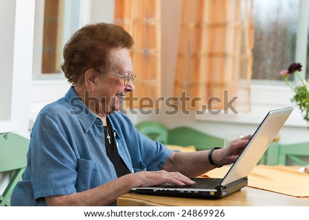 Old woman with a laptop writes e-mail - stock photo