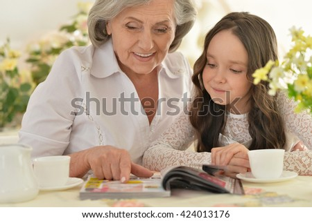 Old woman with a young girl drinking tea - stock photo