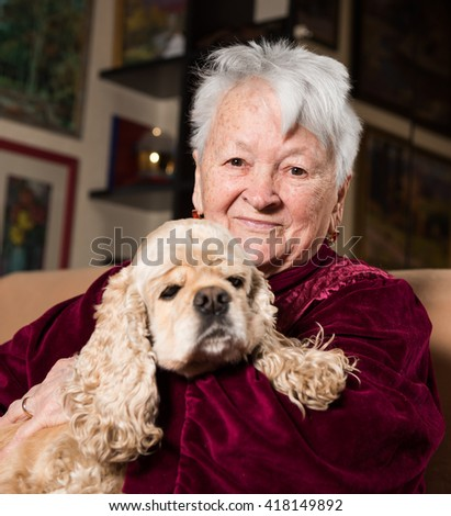 Old woman with american spaniel at home - stock photo