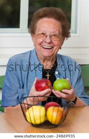 Old woman with apple for the daily Vitmaine - stock photo