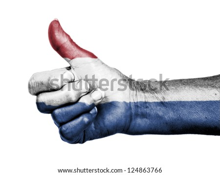 Old woman with arthritis giving the thumbs up sign, wrapped in flag pattern, Holland - stock photo