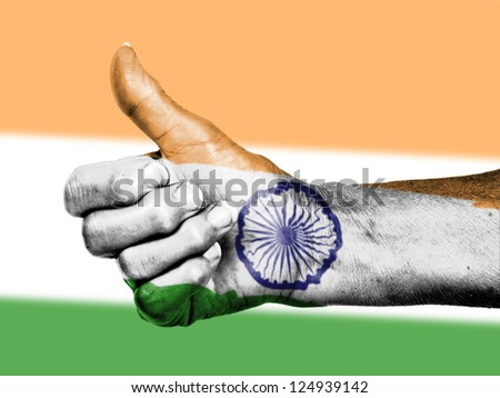 Old woman with arthritis giving the thumbs up sign, wrapped in flag pattern, India - stock photo