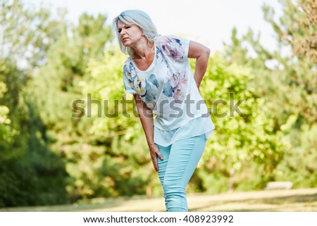 Old woman with back pain while walking in the nature in summer - stock photo