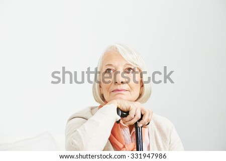 Old woman with cane looking up pensive - stock photo