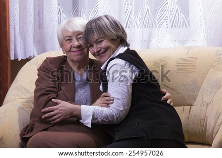 Old woman with daughter hugging - stock photo