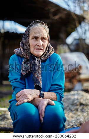 Old woman with head scarf outdoor in the countryside - stock photo