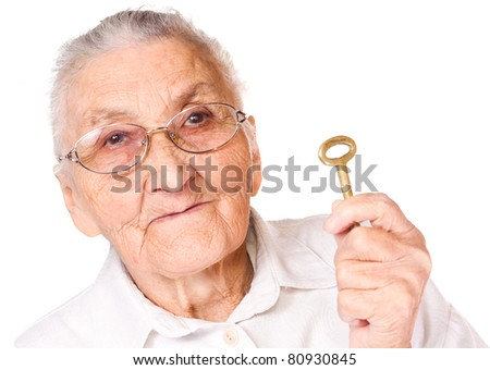 Old woman with isolated background, holding key - stock photo