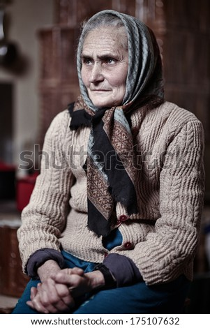 Old woman with kerchief indoors with selective focus - stock photo
