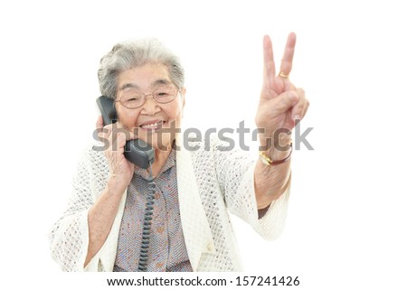 Old woman with phone - stock photo
