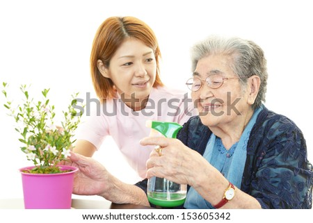 Old woman with plant - stock photo