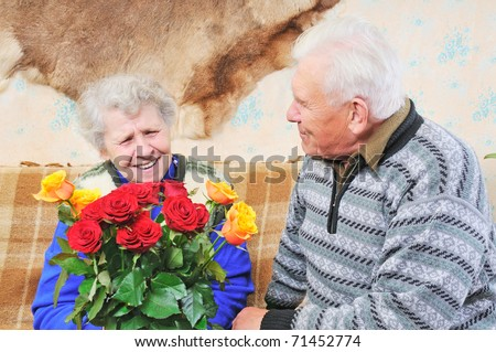 old woman with roses and old man sit near her - stock photo