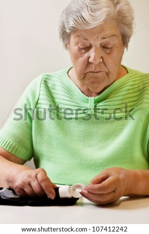old woman with test strips of blood sugar test - stock photo