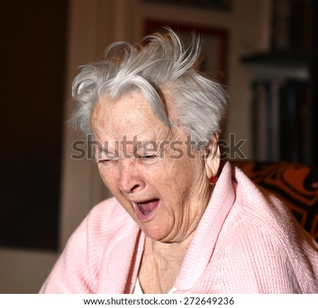Old woman yawning at home