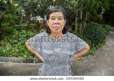 old women of frown in the garden - stock photo