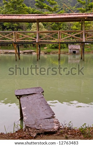 Old wood arbor and walk bridge in river - stock photo