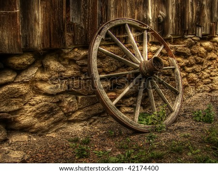 old wood coach wheel around barn - HDR
