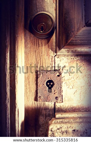 Old wood door with spooky skull keyhole vintage background ideal for Halloween poster. - stock photo