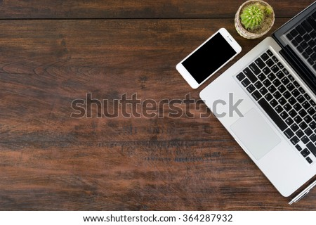 Old wood office desk table with laptop, smartphone and pen. Top view with copy space. - stock photo
