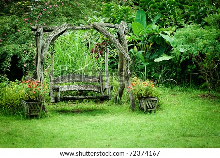 Old wood swing in the green garden - stock photo