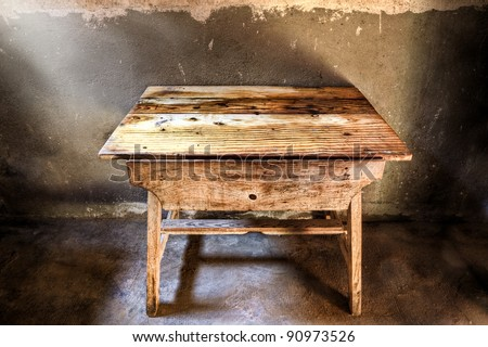 Old wood table in a darkened room illuminated with light from the window.