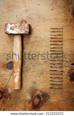 Old wood table with hammer and nails in rustic vintage style. Top view. Retro concept background.  - stock photo