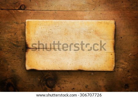 Old wood table with wooden board makes a frame for text in rustic vintage style. Top view. Retro concept background. - stock photo