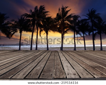 old wood terrace on sea beach with coconuts tree and beautiful dusky sky behind use for multipurpose natural background ,backdrop - stock photo