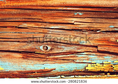Old wood texture with deep cracks and peeling yellow paint - stock photo