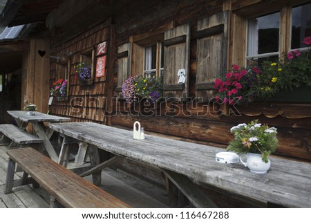 Old wooden Alpine Cabin with outdoor tables and benches in Austria