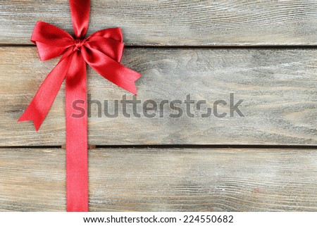 Old wooden background with beautiful bow - stock photo