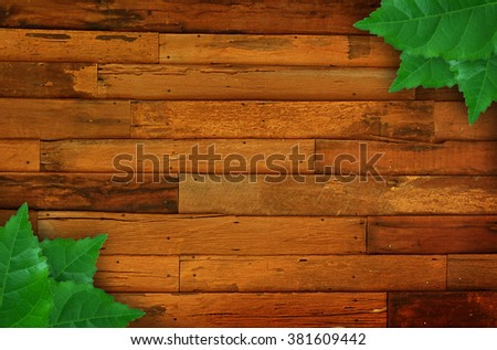 Old wooden background with green leaves frame - stock photo