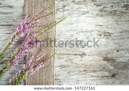 Old wooden background with heather and sacking ribbon - stock photo