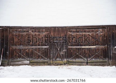 Old wooden barn covered with snow in Poland - stock photo