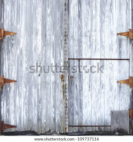 Old wooden barn doors with rusted hinges - stock photo