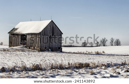 Old wooden barn on plot of open land.  Winter in Wisconsin. - stock photo