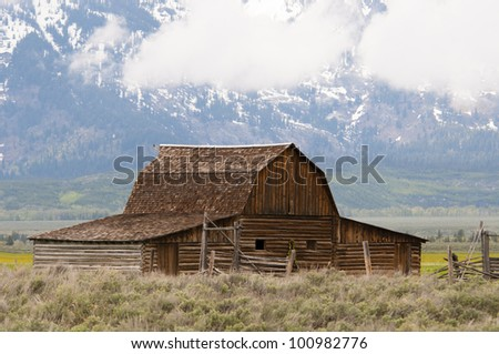 Old Wooden Barn with Grand Teton Mountains in the background - stock photo